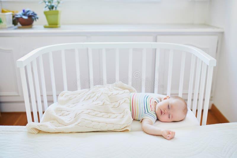 Beb? que duerme en el pesebre del co-durmiente atado a la cama de los padres imagen de archivo libre de regalías