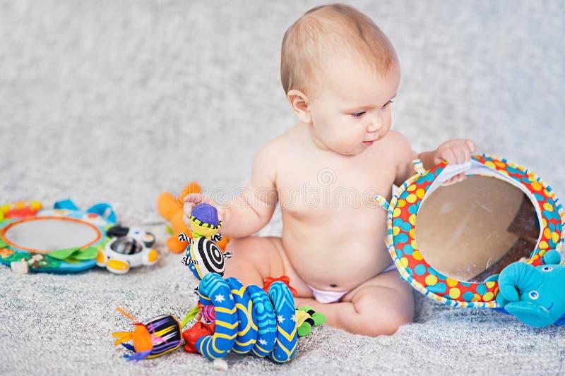 Beb? que encontra-se no tapete tornando-se jogo no m?bil Brinquedos educacionais Crian?a doce que rasteja e que joga com os brinq imagem de stock