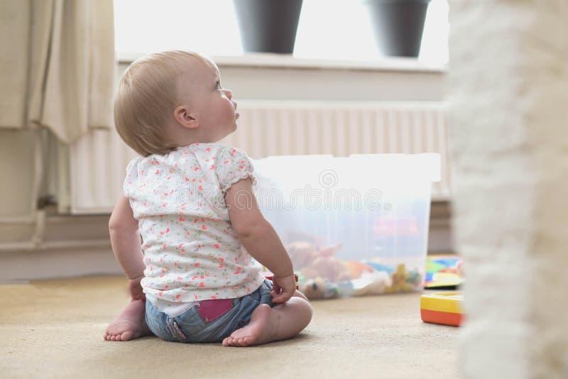Beb? que joga apenas com brinquedos em um tapete no assoalho em casa foto de stock royalty free