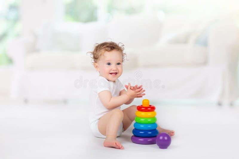Beb? que joga com brinquedos Brinquedo para a crian?a Jogo das crian?as foto de stock