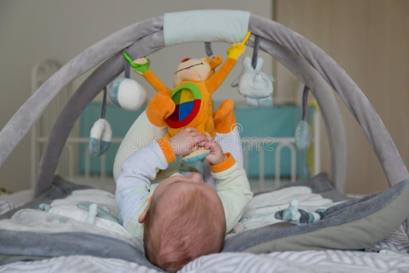 Beb? que juega con los juguetes de la ejecuci?n en la estera que se convierte imagen de archivo