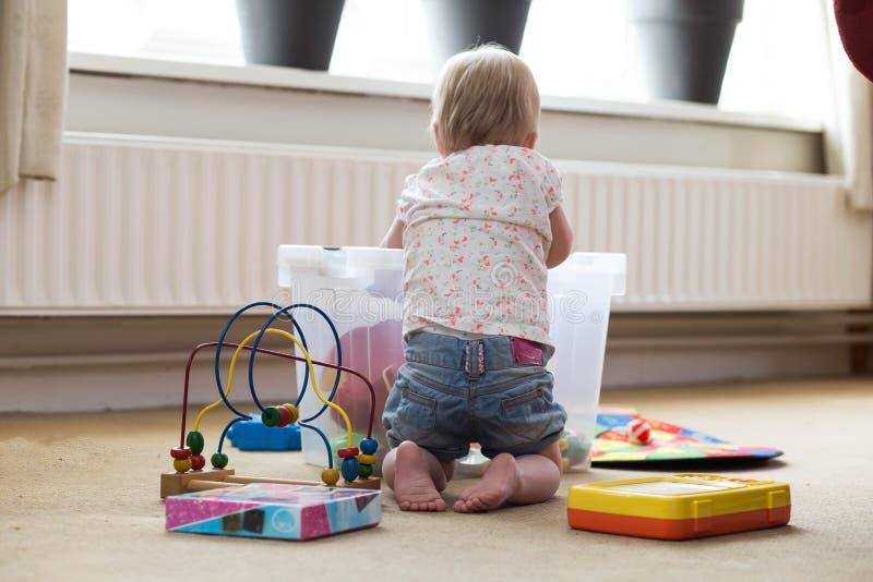 Beb? que juega solamente con los juguetes en una alfombra en el piso en casa imagen de archivo libre de regalías