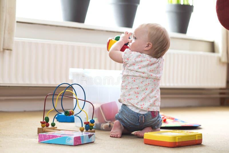 Beb? que juega solamente con los juguetes en una alfombra en el piso en casa imagenes de archivo