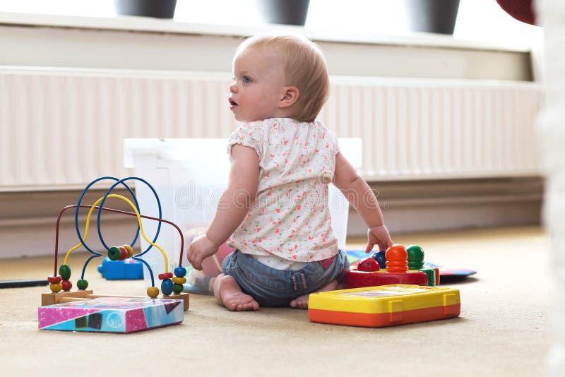 Beb? que juega solamente con los juguetes en una alfombra en el piso en casa fotos de archivo
