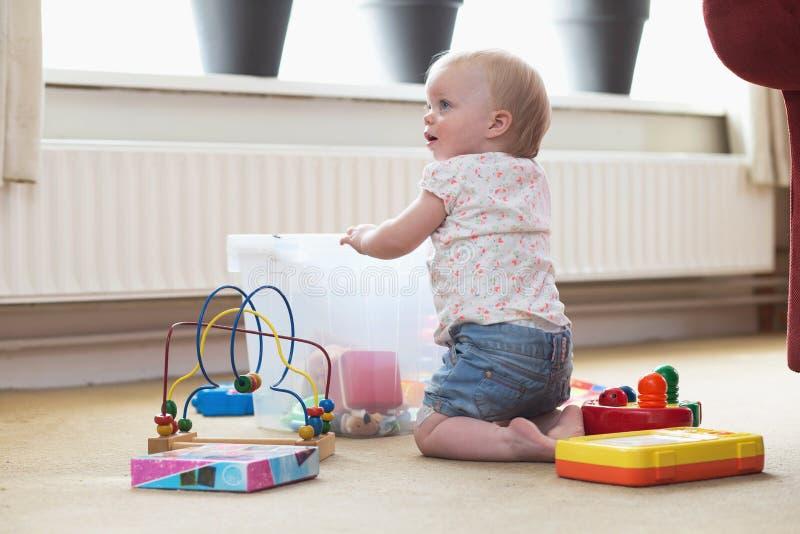 Beb? que juega solamente con los juguetes en una alfombra en el piso en casa foto de archivo libre de regalías