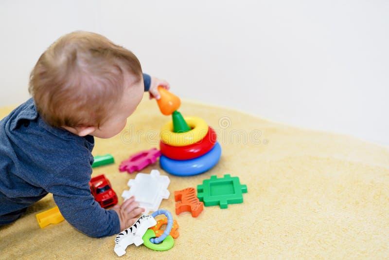 Beb? que smilling e que joga com brinquedos coloridos em casa fundo da crian?a com espa?o da c?pia Desenvolvimento adiantado para fotografia de stock royalty free