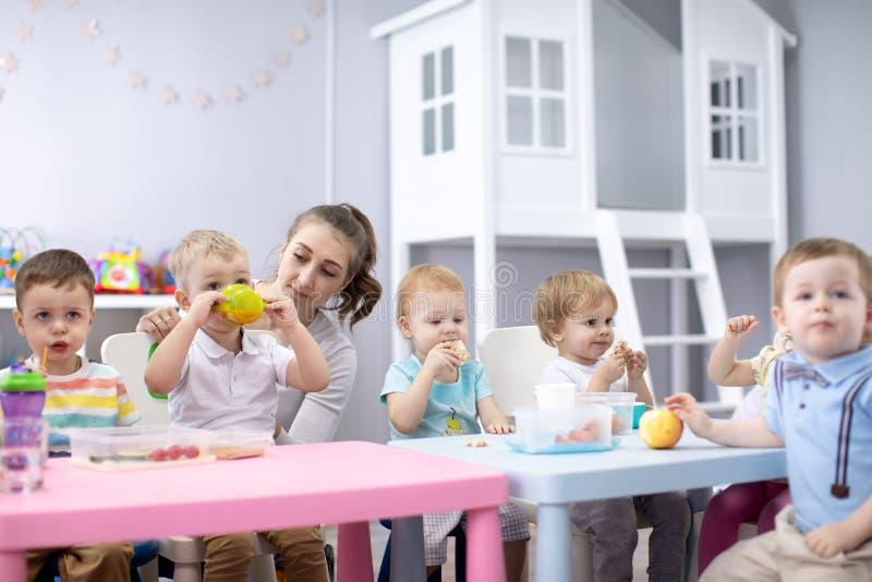 Beb?s que comen el almuerzo sano en cuarto de ni?os o centro de guarder?a imágenes de archivo libres de regalías