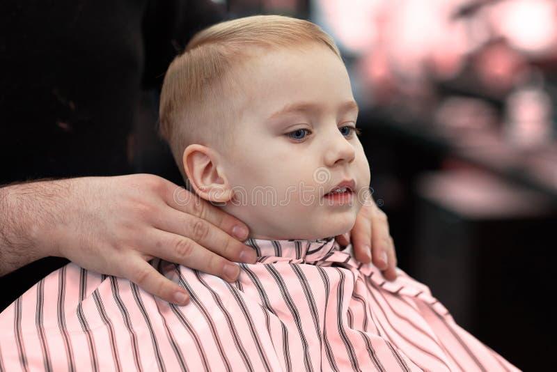 Beb? sonriente rubio lindo con los ojos azules en una peluquer?a de caballeros que tiene corte de pelo del peluquero E imagenes de archivo