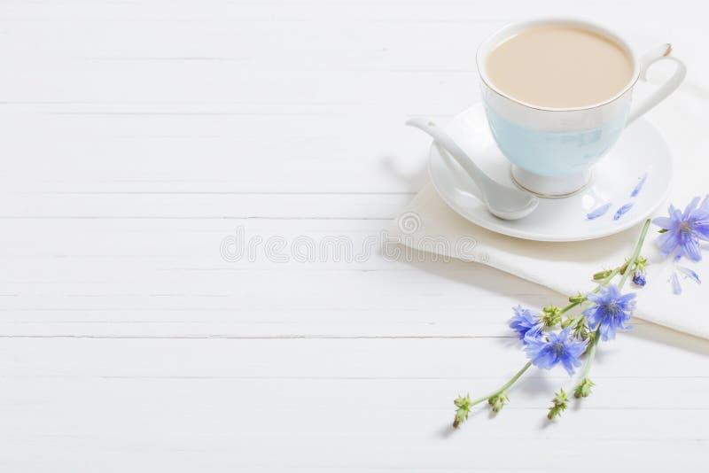 Beba da chicória no copo na tabela de madeira branca foto de stock