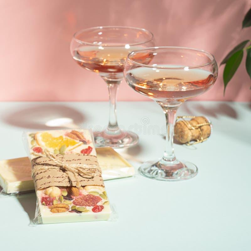Beba o champanhe ou o vinho em dois vidros elegantes e uma barra do chocolate branco Luz solar brilhante do fundo delicado do ros imagem de stock