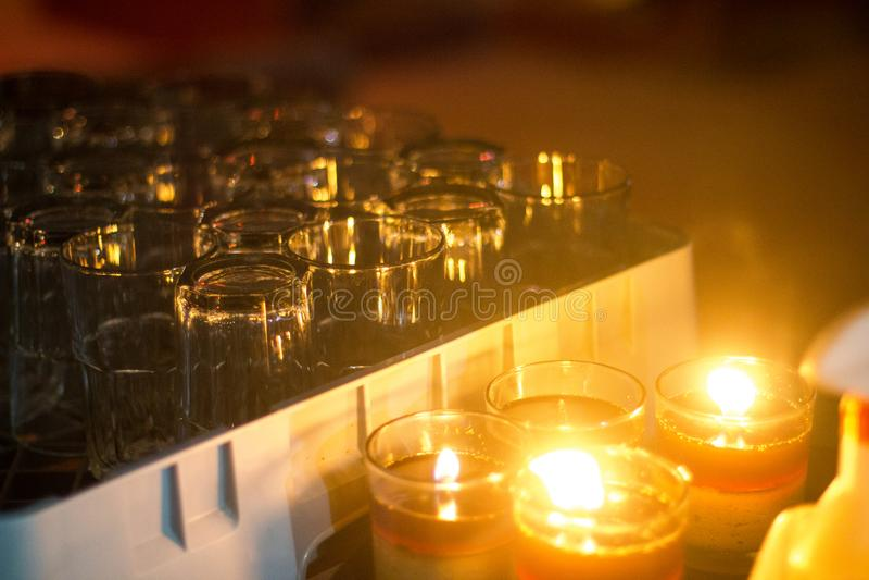 Beba os vidros efervescentes com fulgor alaranjado na luz de vela fotos de stock royalty free