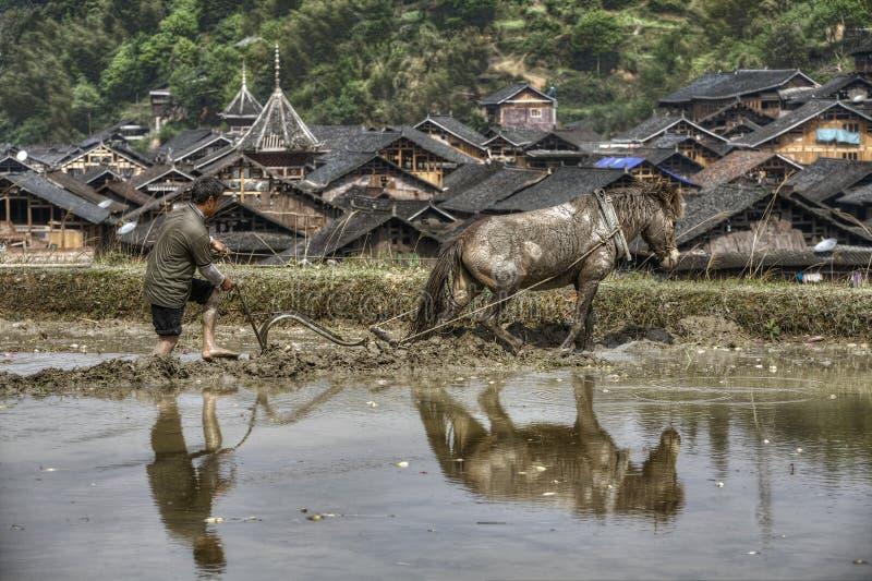 Bebautes Land, Landwirt hinter einem Pflug, der Pferd zieht, Porzellan lizenzfreies stockbild