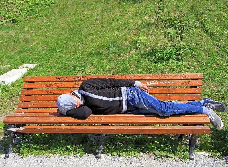 Bebió restos del hombre en un banco en parque imagenes de archivo