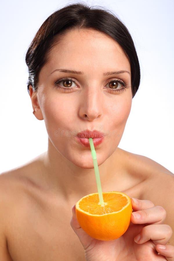 Bebida alaranjada do suco de fruta da vitamina C para a mulher nova foto de stock
