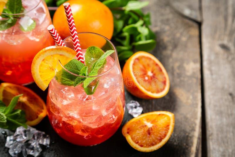 Bebida alaranjada ensanguentado e ingredientes fotografia de stock royalty free