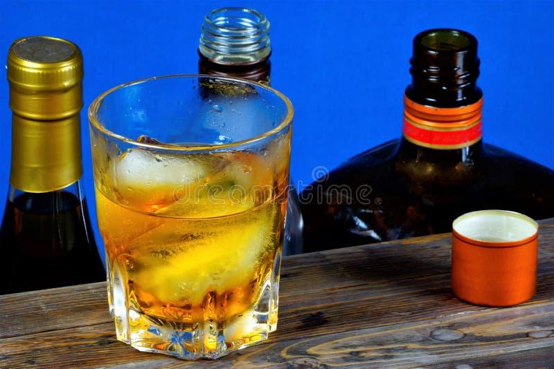 Bebida alcohólica con hielo en la sobremesa de madera, fondo azul Bebida alcohólica aromática fuerte, de diversos tipos de grano  foto de archivo libre de regalías