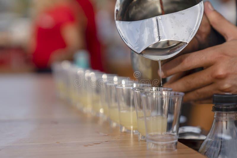 Bebida alcohólica de colada en los vasos de medida en fila foto de archivo