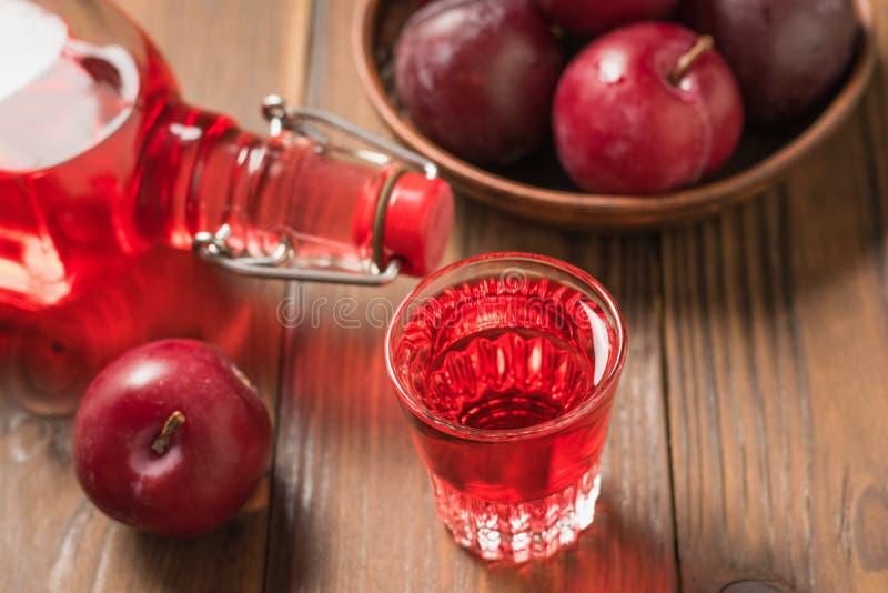 Bebida alcohólica del ciruelo y bayas del ciruelo en la tabla Endecha plana foto de archivo libre de regalías
