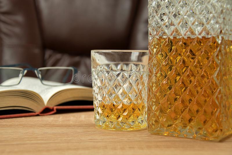 Bebida alcohólica en la jarra cristalina En un whisky vertido de cristal en una tabla de madera en el fondo una silla para asenta foto de archivo libre de regalías