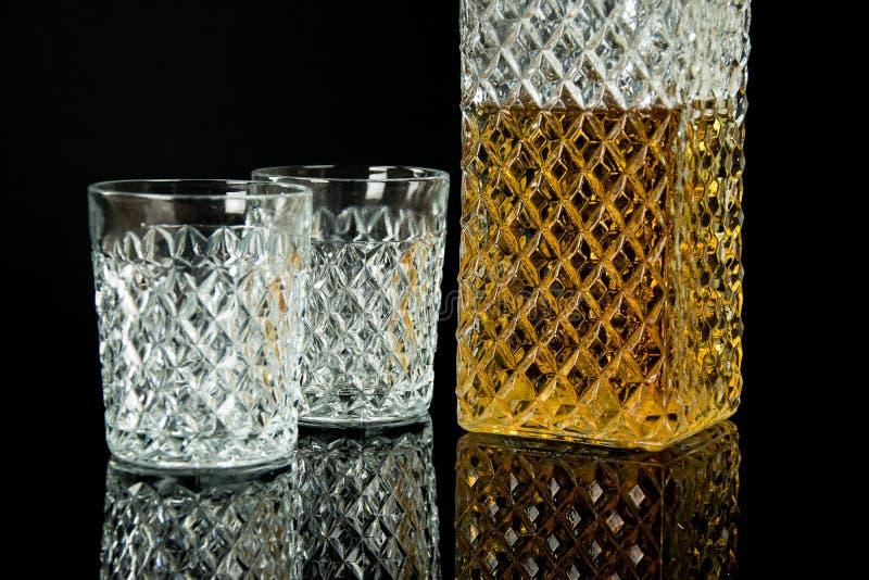Bebida alcoh?lica en la jarra cristalina Dos vidrios vacíos sobre el vidrio negro y el fondo negro fotos de archivo libres de regalías