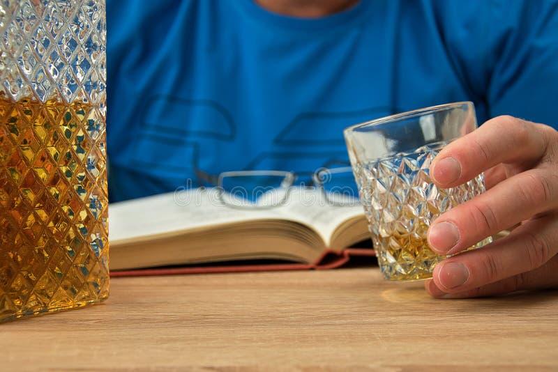 Bebida alcoh?lica en la jarra cristalina El hombre sostiene en su mano un vidrio con una bebida del whisky Abra el libro con los  foto de archivo