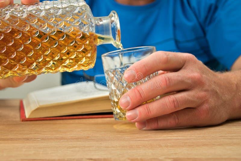 Bebida alcoh?lica en la jarra cristalina Un hombre sostiene un vidrio en su mano y vierte una bebida del whisky Abra el libro con fotografía de archivo libre de regalías