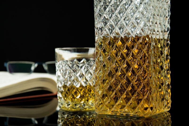 Bebida alcoh?lica en la jarra cristalina En un whisky vertido de cristal sobre el vidrio negro y el fondo negro Abra el libro con fotos de archivo