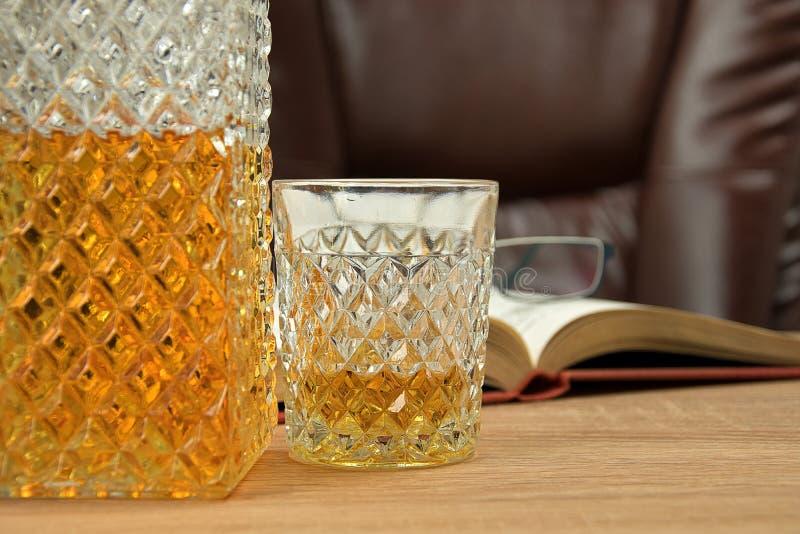 Bebida alcoh?lica en la jarra cristalina En un whisky vertido de cristal en una tabla de madera en el fondo una silla para asenta imágenes de archivo libres de regalías