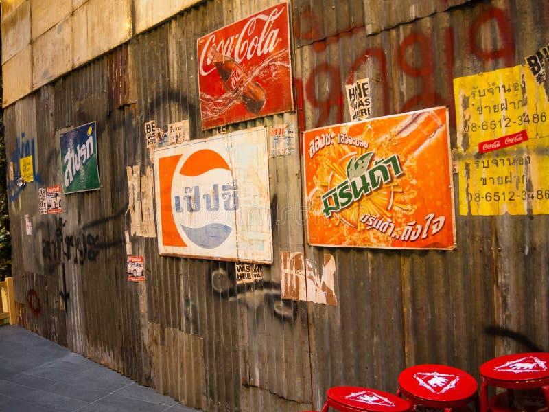 Bebida anaranjada de Mirinda, logotipos del vintage de Pepsi en la versión lingüística tailandesa atados en la pared galvanizada  imagenes de archivo