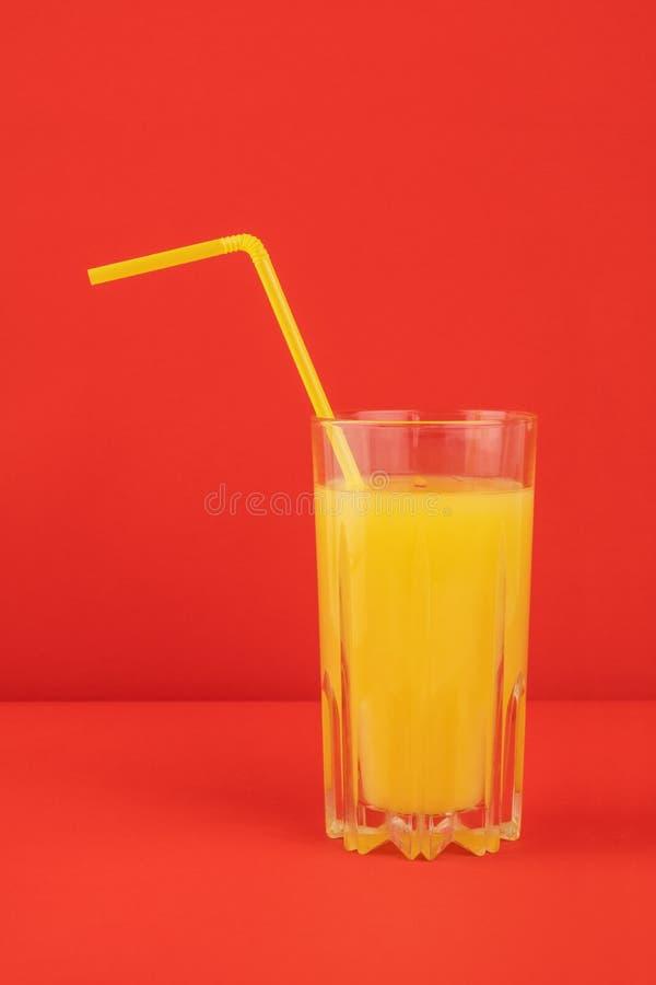Bebida anaranjada del cóctel en fondo rojo Imagen del jugo de la fruta cítrica fotos de archivo
