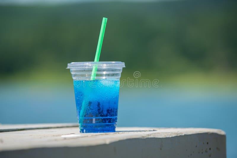 Bebida azul en una taza plástica con una paja verde imagenes de archivo