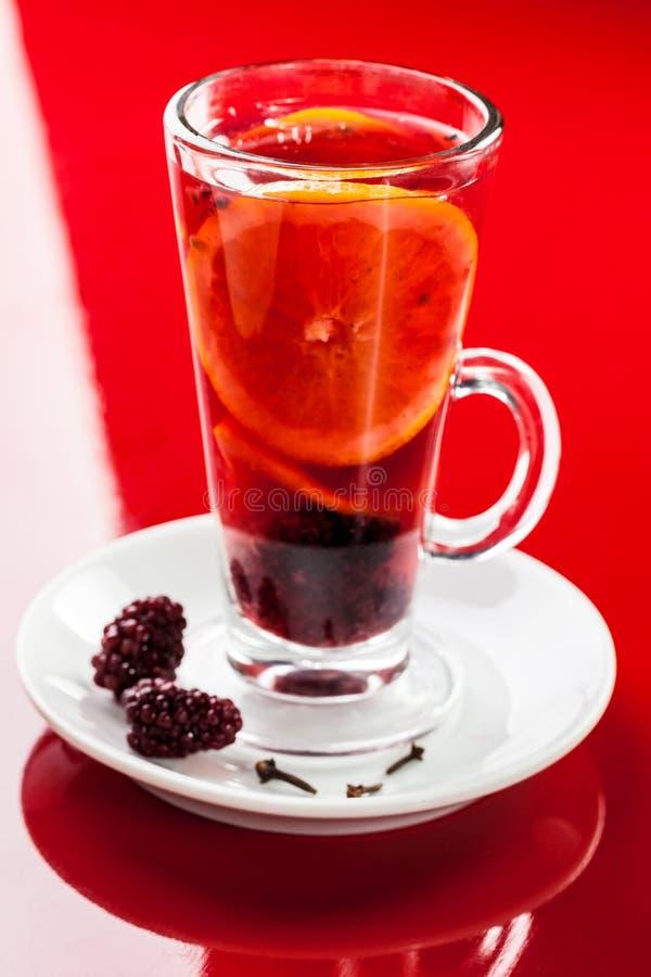 Bebida caliente con la naranja, la zarzamora y los clavos foto de archivo