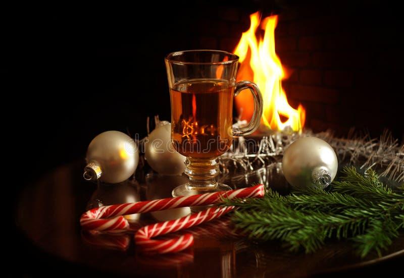 Bebida caliente en vidrio, bolas de la Navidad, ramas del abeto y dulces en un fondo del fuego de la chimenea Año Nuevo y tarjeta fotos de archivo libres de regalías