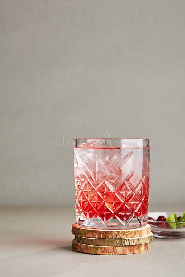 Bebida clara fría de bayas rojas con el hielo, agua, azúcar en un Crys foto de archivo libre de regalías