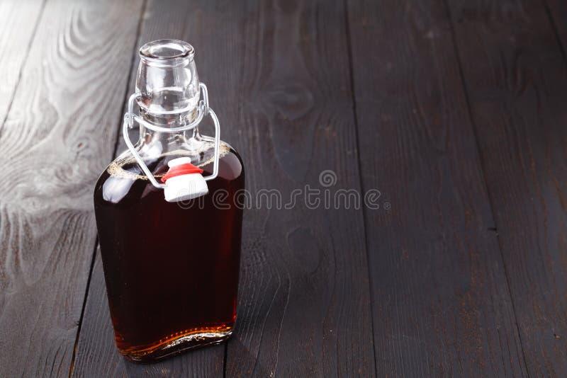 Bebida cordial do álcool caseiro na garrafa na tabela imagens de stock