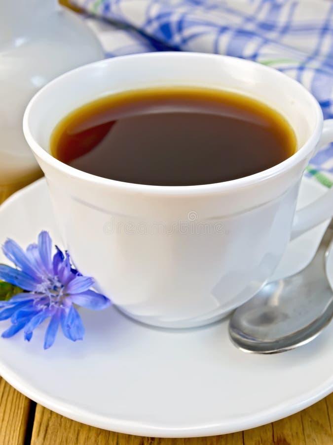 Bebida da chicória no copo branco com leiteiro e flor imagens de stock royalty free