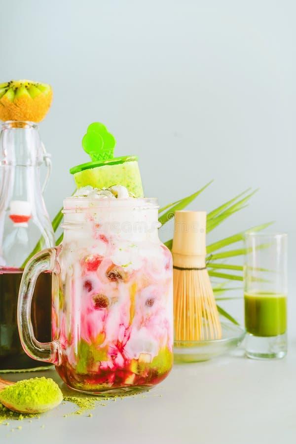 Bebida da fusão de Matcha com gelado do matcha no frasco e nos ingredientes de vidro: café do matcha, frutos vermelhos xarope, le imagem de stock