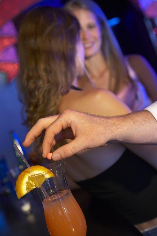 Bebida da mulher drogando-se do homem na barra foto de stock
