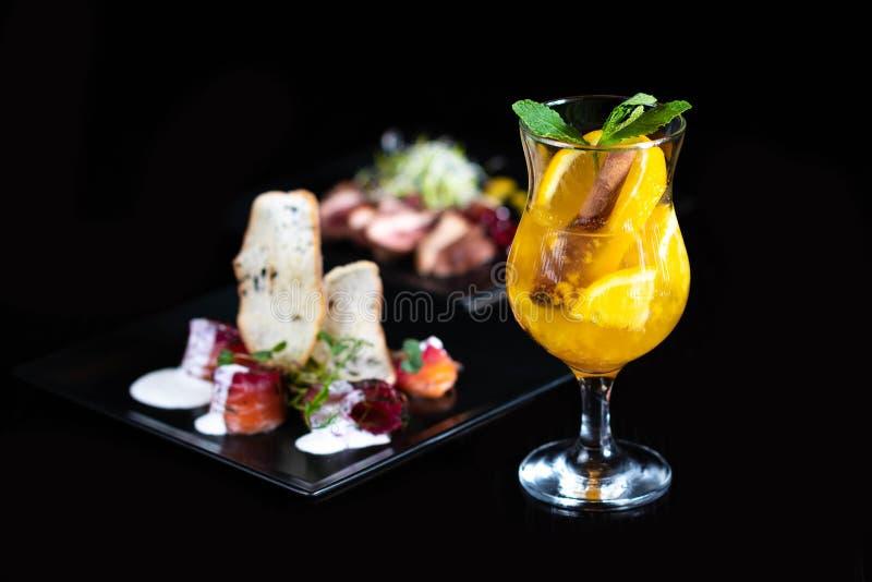 Bebida de aquecimento do inverno com partes de laranja e de especiarias em um fundo preto foto de stock