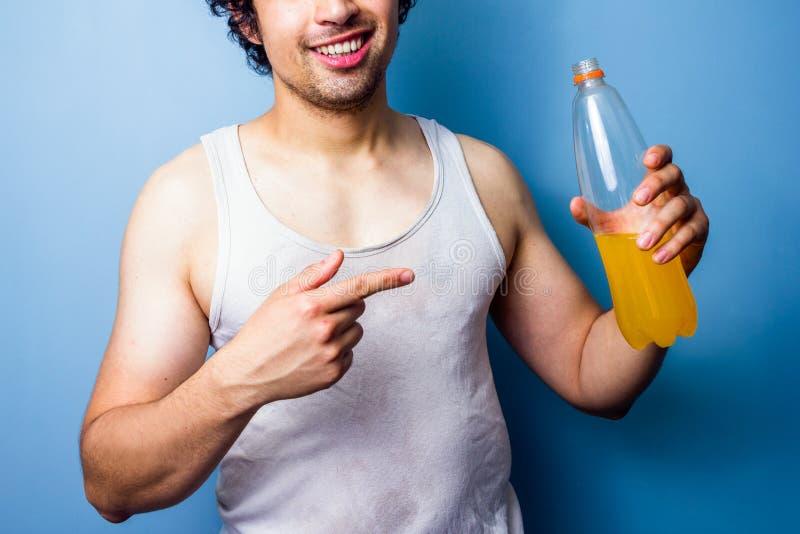 Bebida de consumición de la energía del hombre joven después de un entrenamiento sudoroso imagenes de archivo
