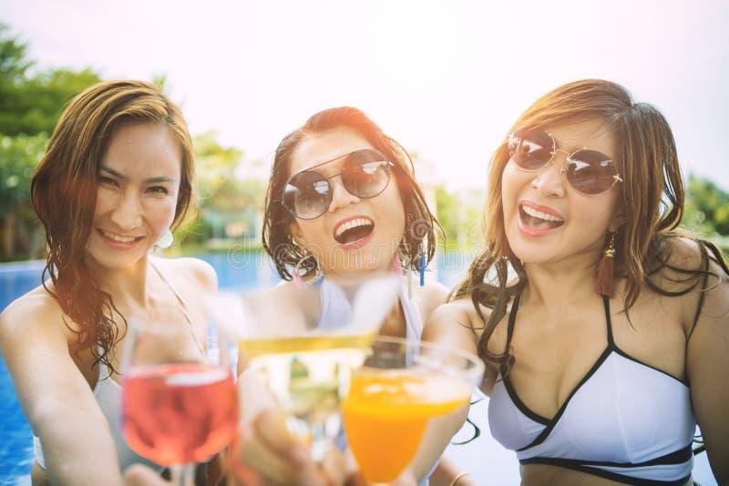 Bebida de consumición de una felicidad asiática más joven de la mujer tres en piscina del waer fotografía de archivo libre de regalías