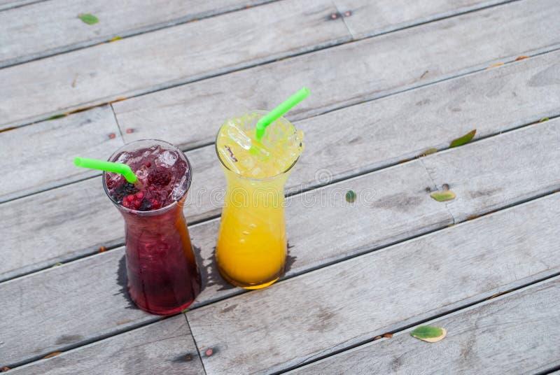 Bebida de la baya, del mango y de la fruta de la pasión de la mezcla del jugo en vidrio alto con color verde de la paja en de mad foto de archivo libre de regalías