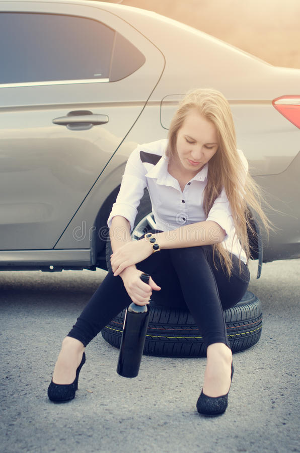 Bebida de la muchacha un alcohol Coche quebrado en un fondo La mujer se sienta en una rueda reparación de la mujer un coche Fondo fotos de archivo