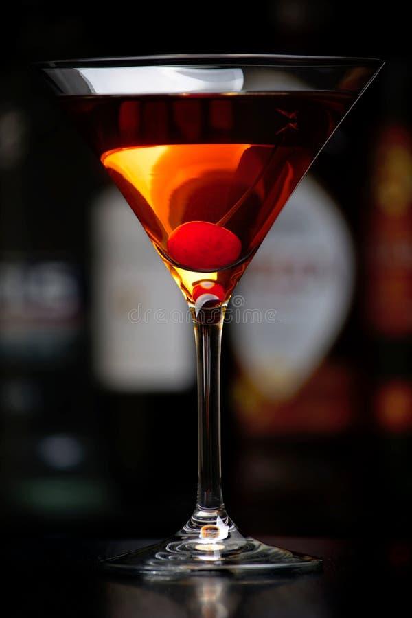 Bebida de Manhattan con la cereza con el club en el fondo fotos de archivo libres de regalías