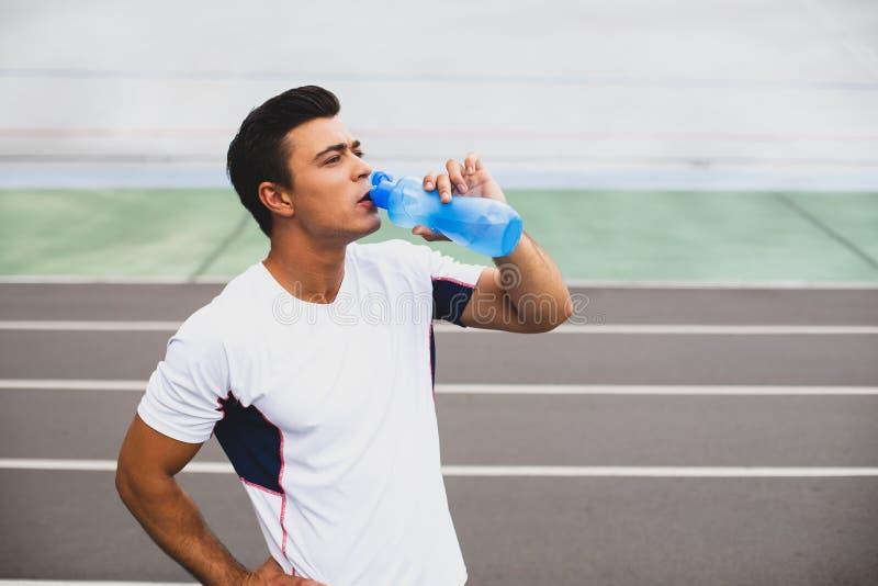 Bebida de prova masculina focalizada após o exercício exterior fotografia de stock royalty free