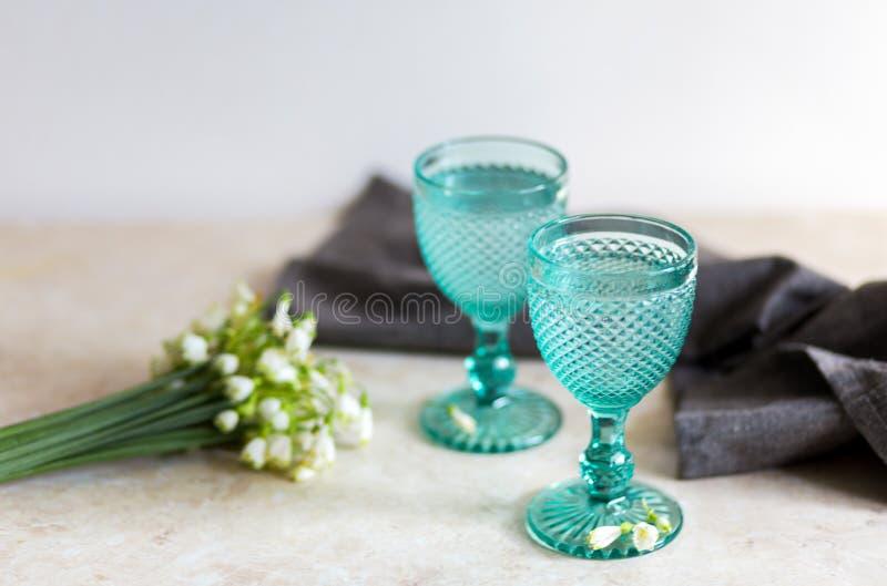 Bebida de Refhesing em uns cálices azuis do vintage no fundo branco com flores srping fotos de stock