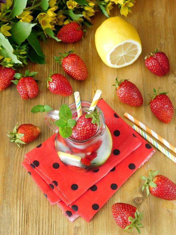 Bebida de refrescamento com cubos, morangos e hortelã de gelo fotografia de stock royalty free