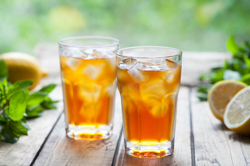 Bebida de refrescamento do cocktail do verão do chá de gelo na tabela de madeira com o propósito do terraço e das árvores Feche a fotografia de stock