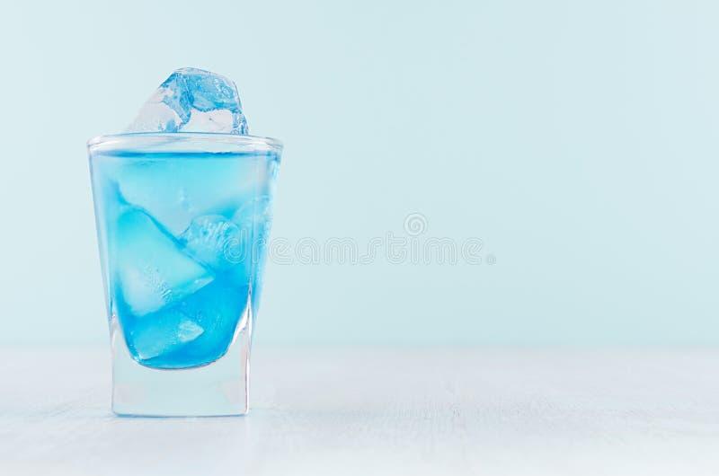 Bebida de refrescamento Havaí azul do álcool no vidro de tiro rico misted com os cubos de gelo no interior pastel moderno da barr foto de stock