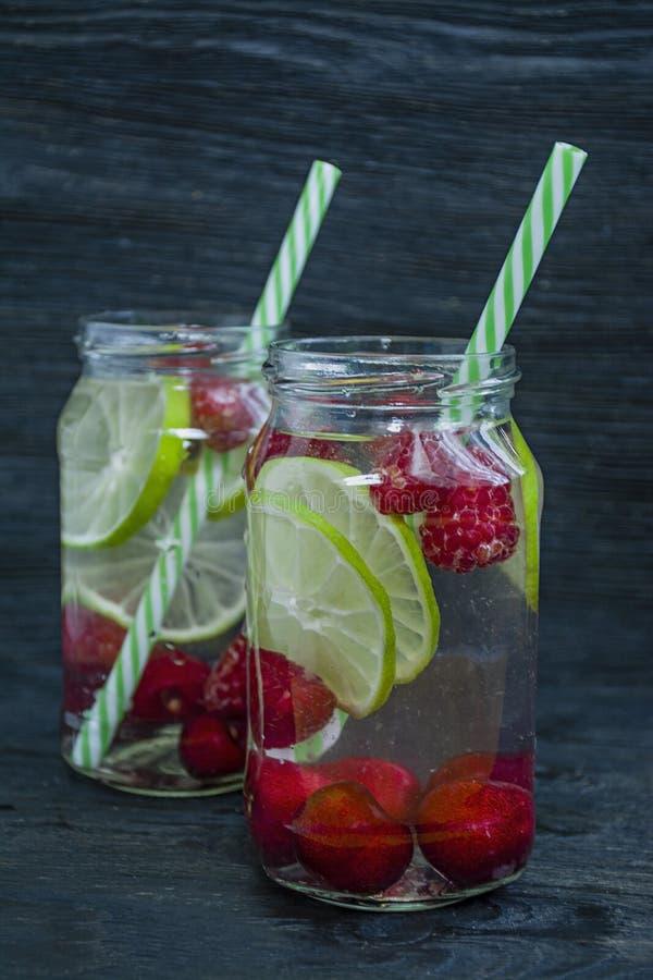 Bebida de restauración del verano con la fruta Bebida hecha de la cereza, frambuesa, cal Fondo de madera oscuro foto de archivo